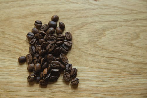 Top view of scattered coffee beans placed on wooden table before making coffee