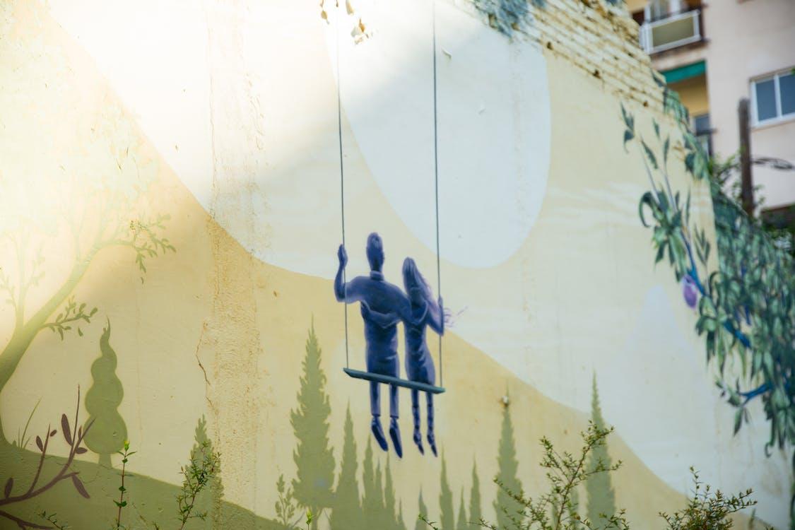 Graffiti of loving couple embracing on swings in moonlight drawn on street wall