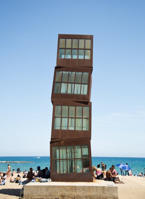 Cubic metal blocks placed on top of each other on concrete stand on sandy beach full of people