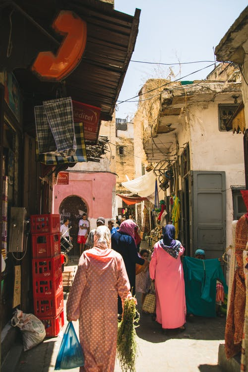 Back view unrecognizable Muslim females in traditional headscarves and modest clothes strolling in local outdoor bazaar on sunny day