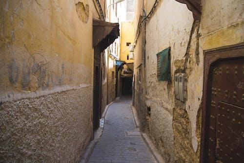 Paved narrow pedestrian walkway between weathered stone residential buildings with metal doors in old Eastern town on sunny weather