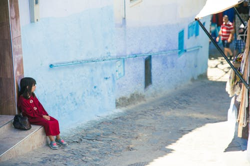 Girl sitting on street stairs in indigenous outdoor market
