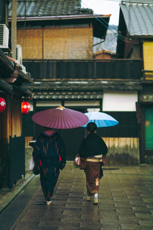 Unrecognizable couple walking with traditional umbrellas