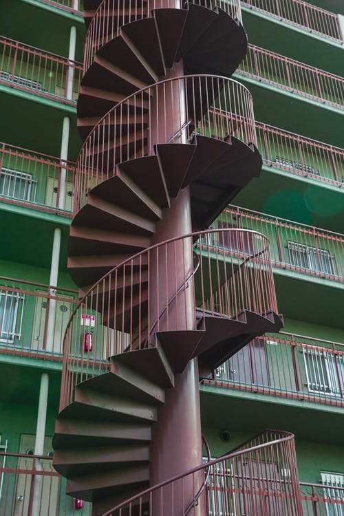 From below of metal spiral stairway located near residential building with green wall in daytime