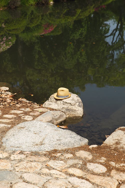 Straw hat located on stone on embankment of lake