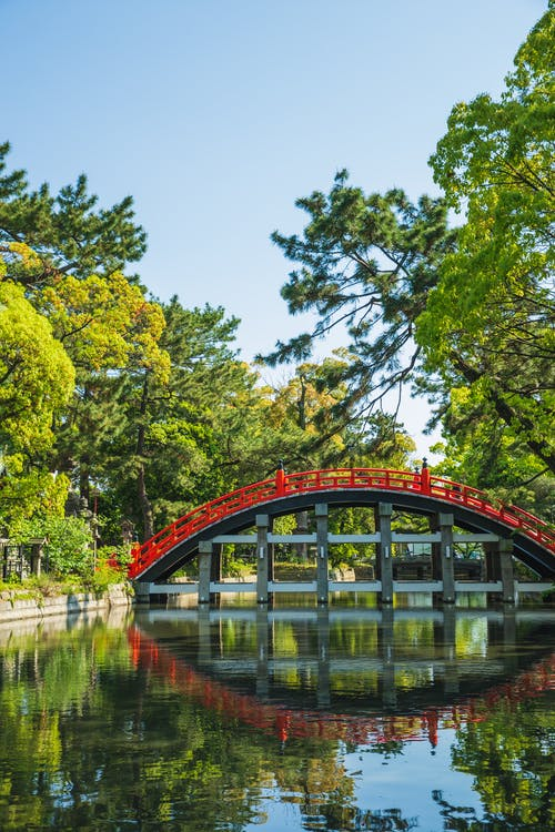 Picturesque view of river with reflection of old oriental footbridge located in green park of Sumiyoshi Grand Shrine Osaka Japan
