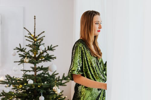 Woman in Green Dress Standing by the White Curtain Looking Outside