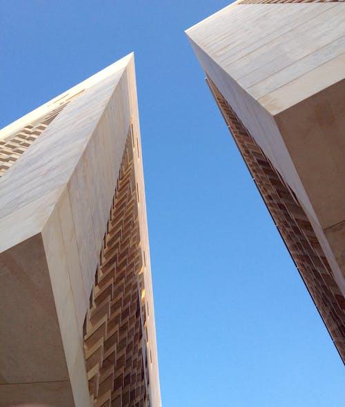Contemporary geometric buildings against blue sky in sunlight