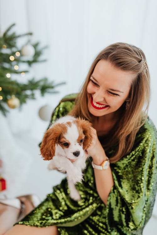 Smiling Woman in Green Dress Holding Her Cute Puppy