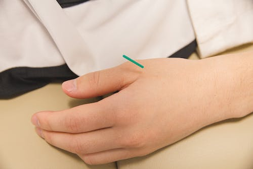 Green Plastic Stick on Persons Hand
