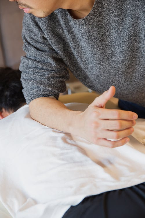 Man doing massage to patient lying on couch