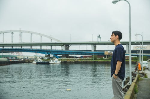 Man in Blue Crew Neck T-shirt Standing Near Body of Water
