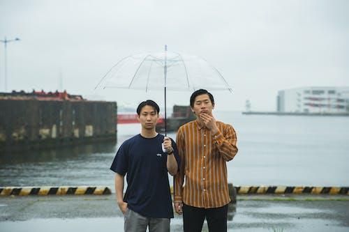 Man in Black Crew Neck T-shirt Holding Umbrella Beside Woman in Brown Coat