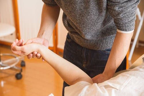 Crop chiropractor massaging hand of patient