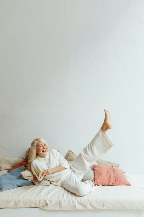 Woman in White Robe Lying on Bed