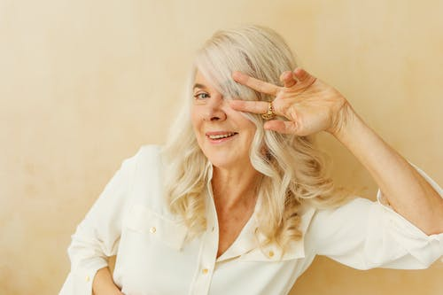 Smiling Elderly Woman Doing a Peace Sign while Looking at Camera