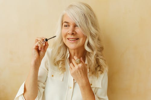 Smiling Elderly Woman Holding a Mascara Brush