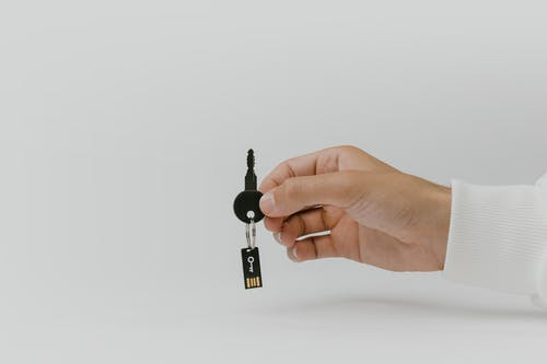 Person Holding Black and Silver Key