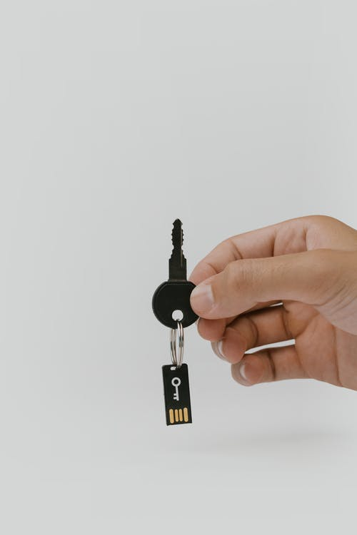 Hand Holding a Key With a USB Flash Drive