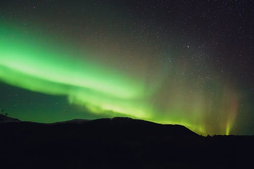 Bright green northern lights above mountain at night