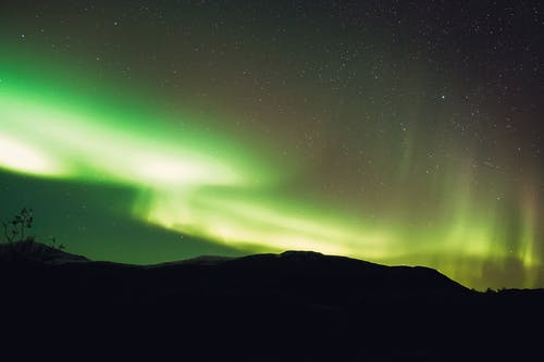 Low angle scenery view of bright green northern lights illuminating mountain silhouette and starry sky in evening