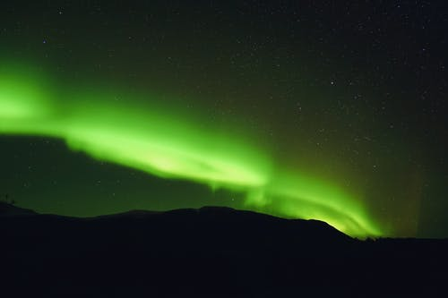 Bright green aurora in starry sky over mount in twilight