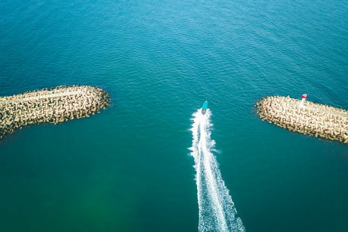 Drone view of fast boat sailing near embankment in turquoise sea with rippled water