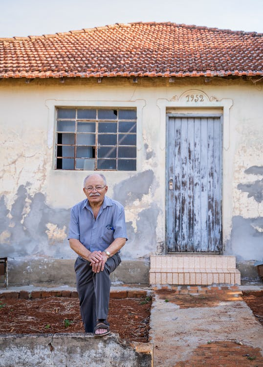 Elderly man near old house with rough walls