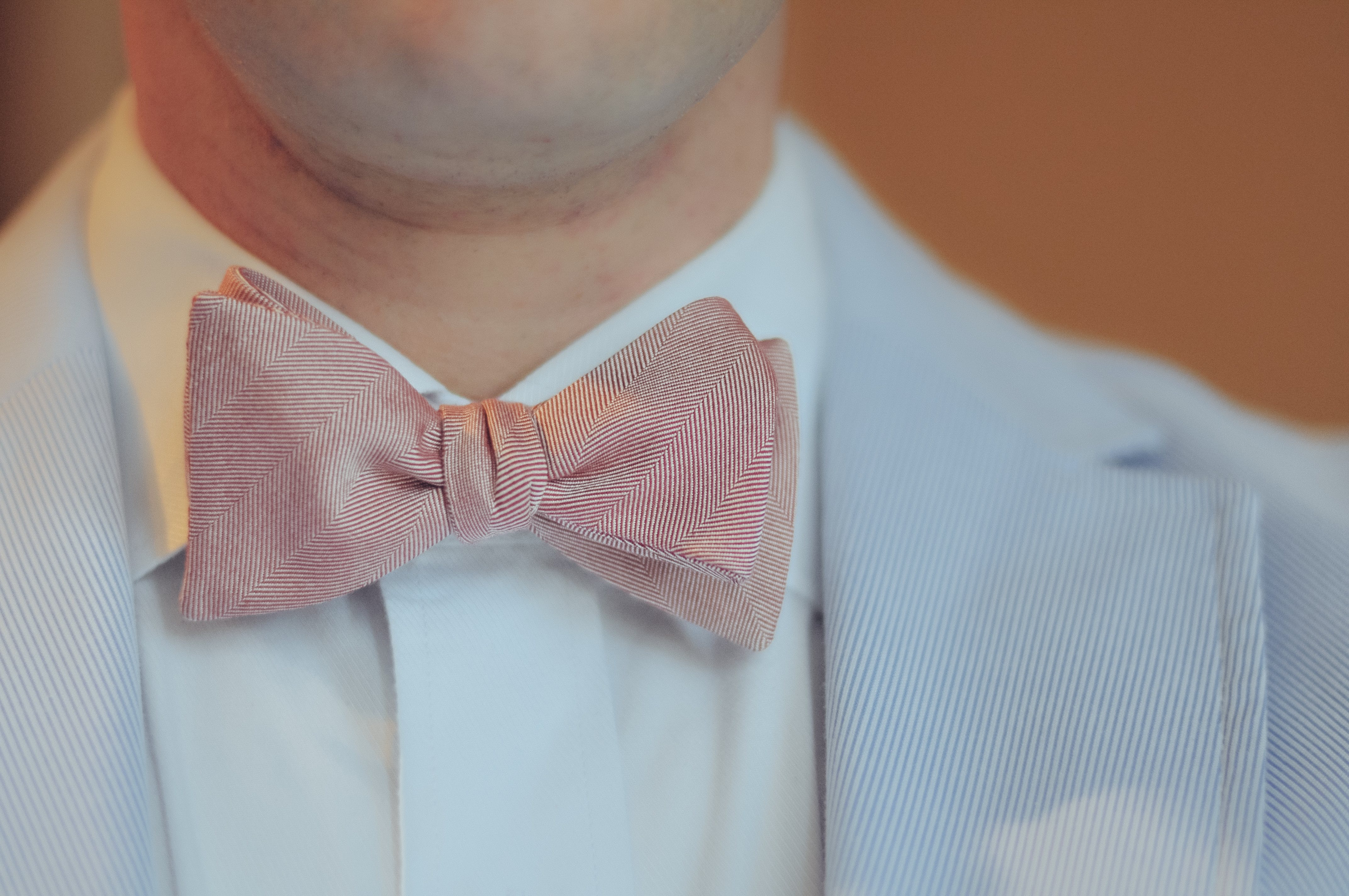 Close-up Photography of Person Wearing Pink Bow-tie and Gray Notched Lapel Suit