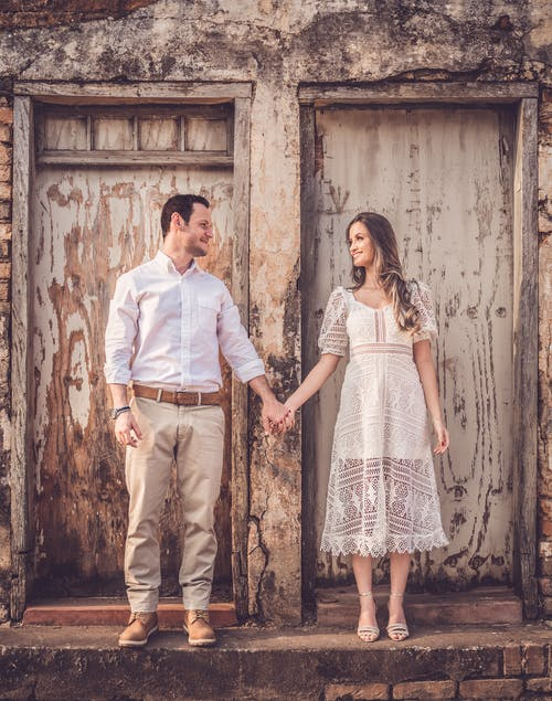Happy couple in stylish apparel holding hands near old building