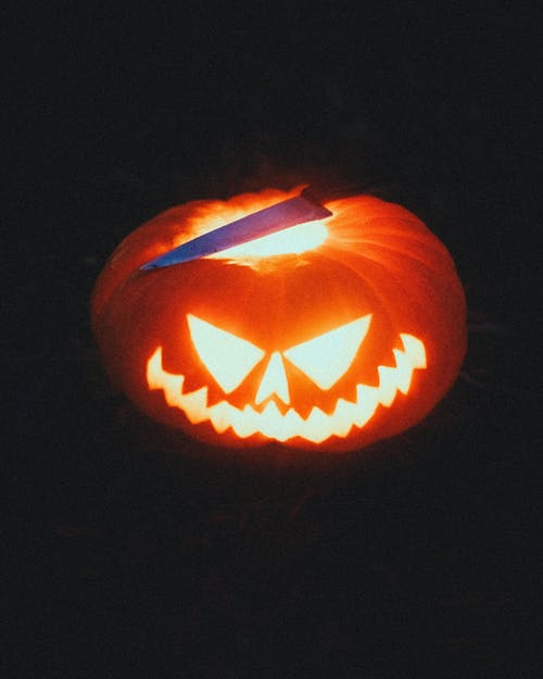 Shiny carved pumpkin and knife on Halloween night