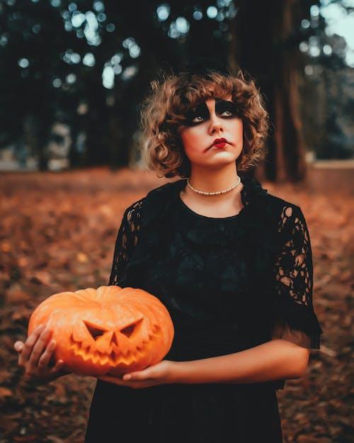 Mujer Reflexiva De Moda Con Calabaza Decorativa Y Maquillaje Durante Halloween