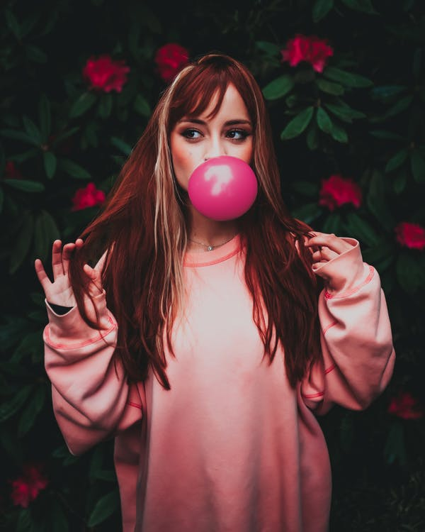 Dreamy woman in trendy clothes blowing pink gum in garden
