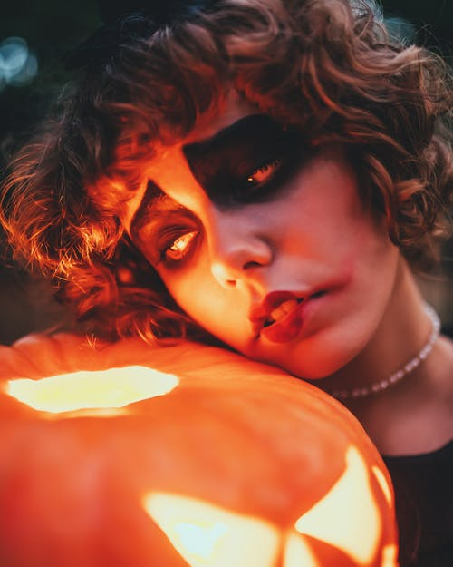 Crop sad female with terrible makeup and curly hair leaning on shiny carved pumpkin on Halloween night while looking away