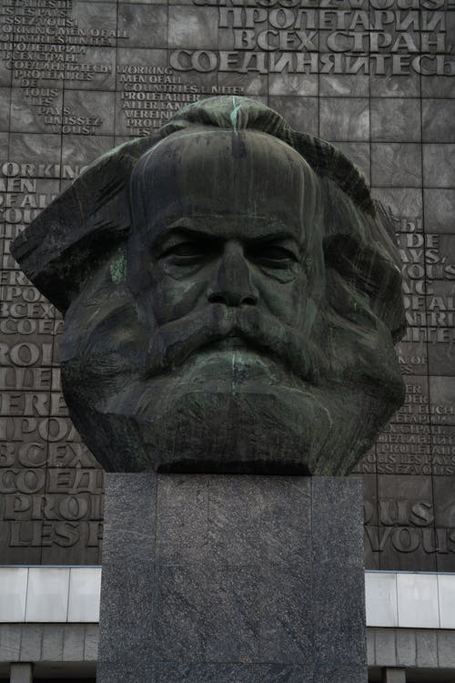 Stone head sculpture of revolutionary placed on high postament against stone wall in city