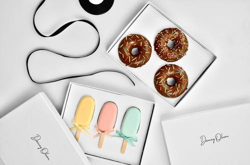 Overhead view of collection of colorful doughnut and ice lolly shaped handmade soap in gift boxes near rolled ribbon