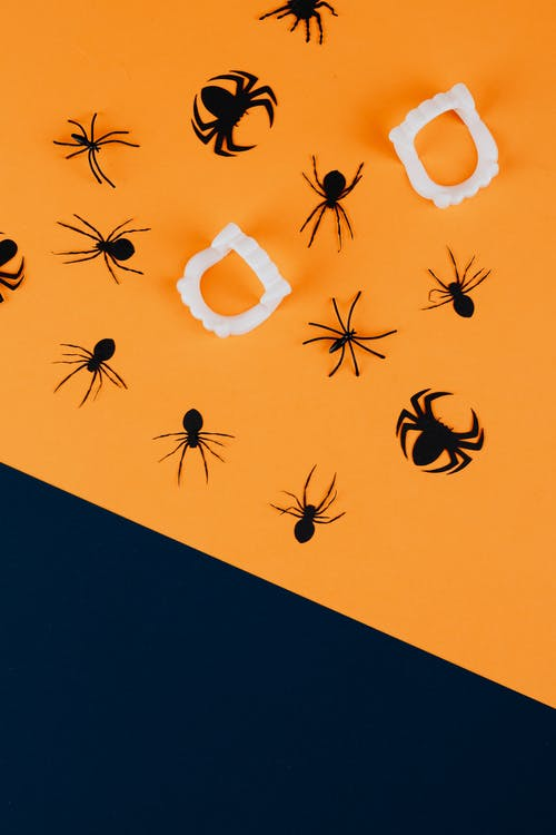 Black Paper Spiders and Vampire Fangs on Orange Background