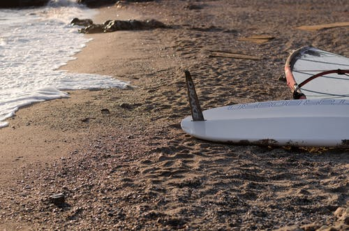 White Surfboard on Brown Sand Near Body of Water