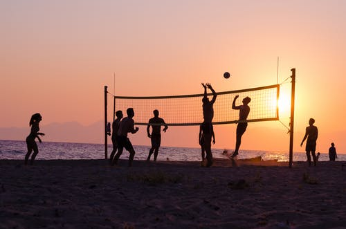 Silhouette of People Playing Volleyball on Beach during Sunset