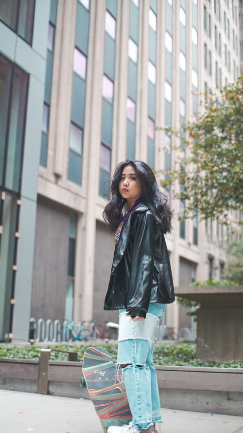 Woman in Black Leather Jacket Standing Near White Concrete Building