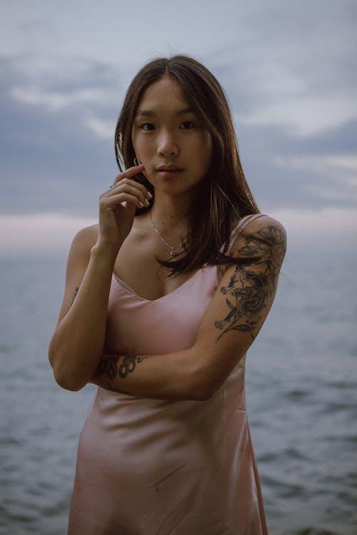 Calm young trendy Asian woman resting near sea at sundown