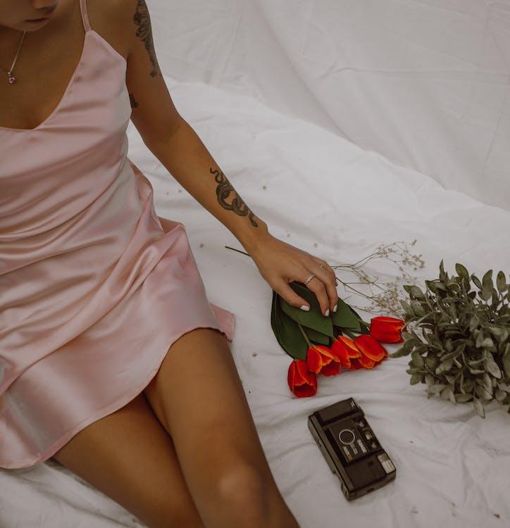 Обрезать соблазнительную женщину, сидящую на кровати с цветами и ретро фотоаппаратом