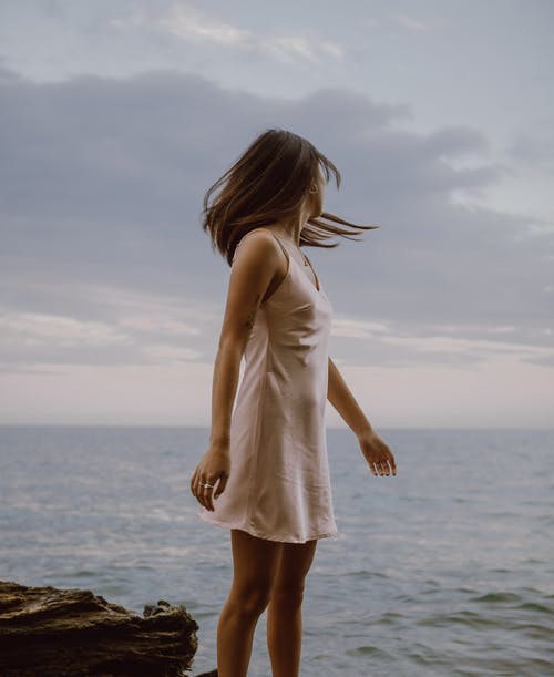 Side view of anonymous young female tourist in mini dress standing on rocky coast and admiring waving sea against cloudy sunset sky