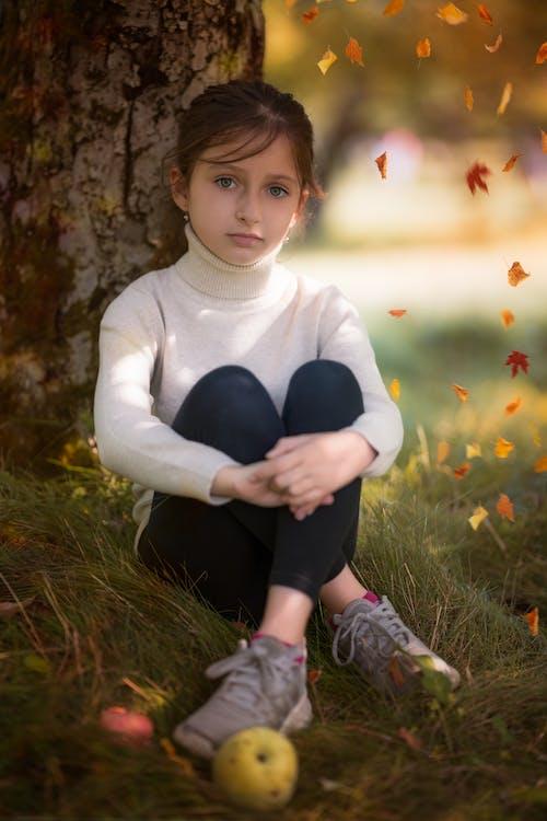 Calm little girl recreating near tree in autumn park