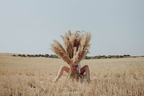 Unrecognizable woman hiding behind dried grass