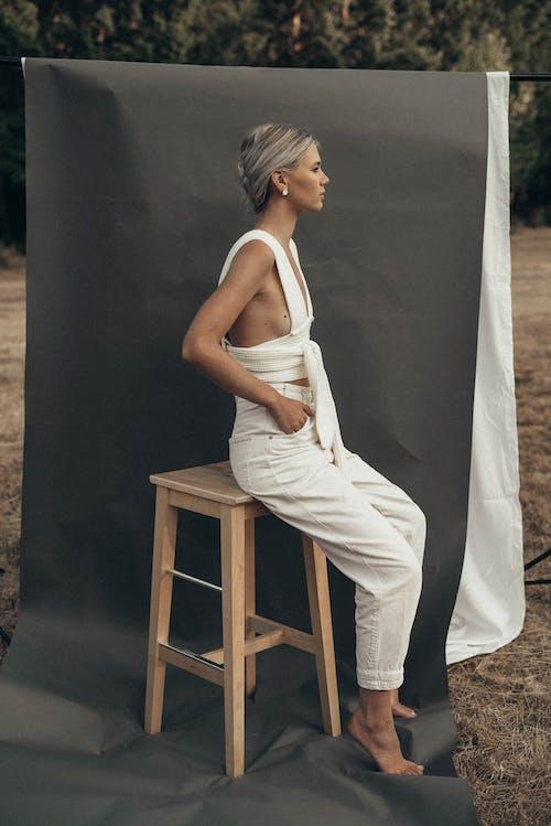 Stylish woman sitting near gray textile