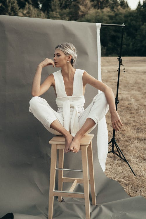 Graceful woman sitting on stool in nature
