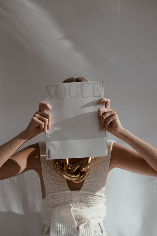 Unrecognizable female with big chain on neck standing on white background while covering face with fashion magazine in sunlight