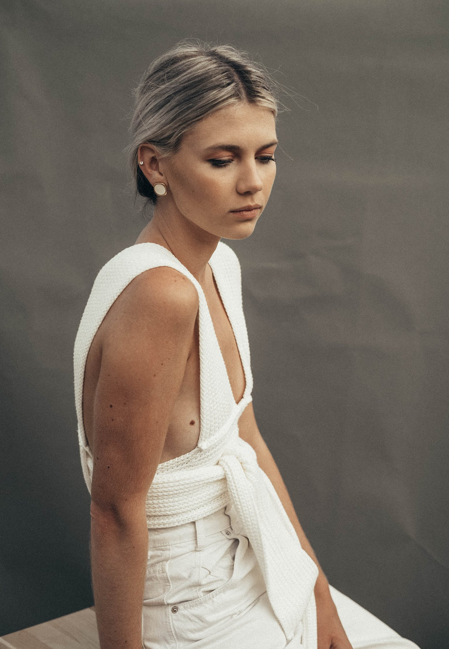 Thoughtful female with tucked back hair in white clothes wearing earrings looking down while sitting on chair on gray background