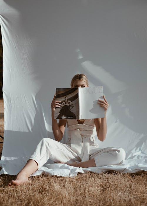 Unrecognizable woman reading magazine in nature